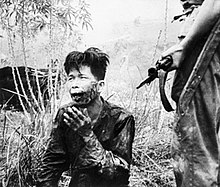 A scarred and bloodied man of Oriental appearance kneels on the ground. Beside him stands a man with an FN FAL battle rifle. A bayonet is fixed to the end of the rifle.