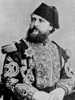 Mott as an Egyptian military officer, a middle-aged man with a full beard wearing an elaborate uniform with a fez