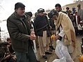 The Nawbahar district chief of police, left, helps an Afghan villager with bags of beans in Pinzo village, Nawbahar district, Zabul province, Afghanistan, Feb 120205-N-UD522-099.jpg
