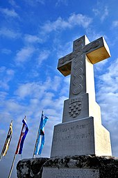 View of a large stone cross carved with the Croatian coat of arms. Outlined against the blue sky are the cross and three vertically hung flags.