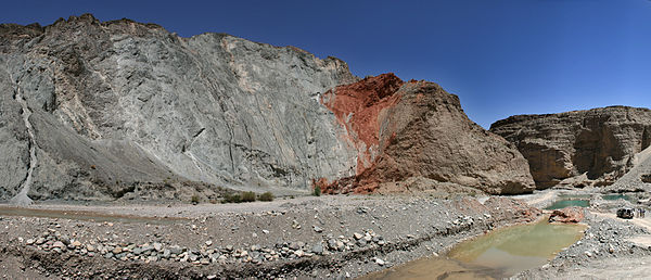 Thrust fault in the Qilian Shan, China. The older (left, blue and red) thrust over the younger (right, brown). Thrust fault Qilian Shan.jpg