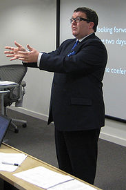 Large man in suit, glasses and short dark hair giving a presentation in front of overhead projection screen