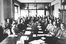 Photo of a caucus meeting showing thirty-five men and a woman, sitting around several long tables with documents laid out before them. As space is cramped and there is not room for everyone at the table, they are seated in two rows.