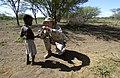 US Navy 060811-N-0411D-027 U.S. Marine Staff Sgt. Jesse Peters helps a local Pokot tribe boy to open a portion of a military food ration (MRE) given to him by a U.S. service member.jpg