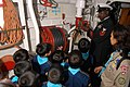 US Navy 061015-N-5334H-201 Chief Quarter Master Corey King explains the ship's fire main system to children and adults from the Cub Scouts Tokyo Group ^4,.jpg