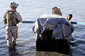 US Navy 080711-M-1391M-015 A boy watches as Gunner's Mate 2nd Class Shawn Sass, assigned to Riverine Squadron (RIVRON) 3, approaches his boat for inspection on the Watah Peninsula, near Rawah.jpg