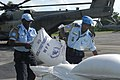 US Navy 080910-N-3595W-442 Haitian National Police work with military personnel embarked aboard the amphibious assault ship USS Kearsarge (LHD 3) to prepare food and water supplies for distribution.jpg