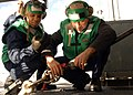 US Navy 090215-N-4408B-106 Aviation Machinist's Mate Schal M. Bodu and Aviation Machinist's Mate John Monrouzeau adjust the safety hold-back of a jet engine trailor.jpg