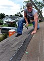 US Navy 090611-N-9712C-001 Aviation Electronics Technician 2nd Class Sonny Abernathy nails shingles to the roof of a Habitat for Humanity house.jpg