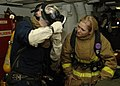 US Navy 091020-N-5019M-048 Hull Technician 2nd Class Jason Nicholson demonstrates how to don an MCU-2P chemical, biological, and radiological protective mask to Hull Technician Fireman Apprentice Sara Bingham.jpg