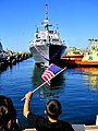 US Navy 100423-N-4774B-136 Friends and family members of Sailors aboard USS Freedom (LCS 1) wave flags and signs to greet them after completion of her maiden deployment.jpg
