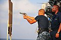 US Navy 110406-N-ZS026-059 Aviation Ordnanceman 3rd Class Rayjuan Horton fires a 9mm pistol from behind cover during a small arms practical weapons.jpg