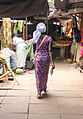 Walking woman with a fish in her hand Gambia.jpg