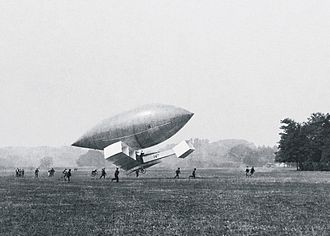 Santos-Dumont 14-bis - The 14-bis at the Château de Bagatelle grounds, suspended from the envelope of Santos-Dumont's No.14 airship.