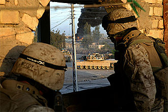First Battle of Fallujah - During the First Battle of Fallujah, U.S. Marines from the 1st Marine Regiment take cover as an M1A1 Abrams from the 1st Tank Battalion fires at a building where insurgent snipers are positioned.