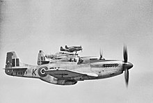 Five World War II-era propeller driven fighters in the air