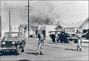 Watts riots - Soldiers of the California's 40th Armored Division direct traffic away from an area of South Central Los Angeles burning during the Watts riot.