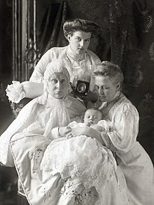 Grand Duchess Alexandra Iosifovna with her daughter, Queen Olga of Greece, her female-line great-granddaughter, Princess Maria of Sweden and female-line great-great-grandson, Lennart. Behind Grand Duchess Alexandra there is a portrait of Olga's late daughter and Maria's mother, Alexandra. (Source: Wikimedia)
