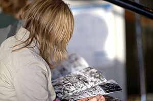 English: Young woman reading a comic book at A...