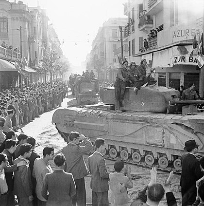 British tank moves through Tunis during the liberation, 8 May 1943 A Churchill tank and other vehicles parade through Tunis, 8 May 1943. NA2880.jpg