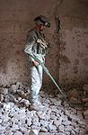 A combat engineer with Company B, 307th Engineer Battalion, 82nd Airborne Division uses a metal detector to search the floor of a house for hidden weapon cache during a raid in Tall Afar, Iraq, Oct. 18, 2005.jpg
