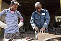 A man prepares a sheet of metal for cutting.jpg