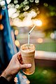 A young man holding a glass of iced coffee at home at sundown. Happy hour non-alcoholic beverage.jpg