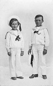 A black and white portrait of two young boys. They are standing alongside one another and are dressed in white sailor uniforms. The shorter boy on the left is smiling and wearing a cap, while the boy on the right has a blank expression and is holding a cap in his left hand.
