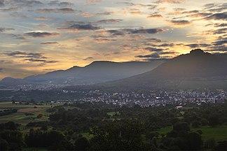 Albtrauf, Mittlere Schwäbische Alb, gesehen vom Osthang (575m) des Jusibergs (672,6m). Die Orte sind Neuffen und Beuren. Den Albtrauf bilden Hohenneuffen (745,4m), Bassgeige (735,6m), westlich von Beuren der Engelberg (527,2m) und weiter hinten der Teckberg (774,8m) mit vorgelagertem Schwäbischen Vulkan Hohenbol (602,2m). Am Albtrauf liegt ausladender Hangschutt. Das Vorland mit den beiden Orten ruht auf Schichten des Braunen Jura.