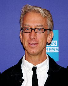 A smiling Andy Dick with glasses, wearing black and white clothes with an American Express logo behind him