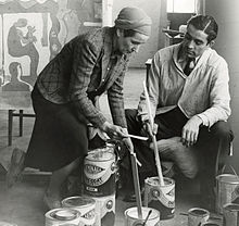 Reeves and an unidentified male assistant stirring paint for a mural
