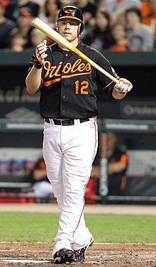 A man, wearing a black batting helmet, a black baseball uniform with the Baltimore Orioles script logo and the uniform number 12 across his chest, clutches his bat with his left hand.