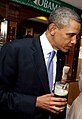 Barack Obama watches while Michelle Obama pours a pint of stout (cropped).jpg
