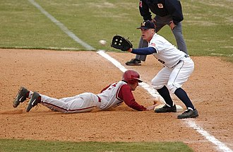 Baseball - A first baseman receives a pickoff throw, as the runner dives back to first base.