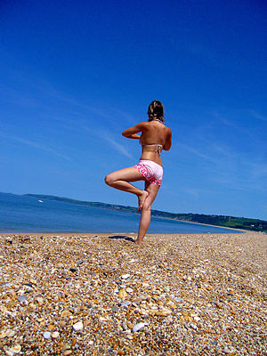 Girl practicing yoga at the beach