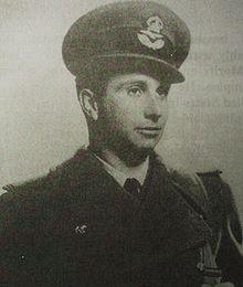A young man dressed in a military uniform, including coat and hat with insignia.