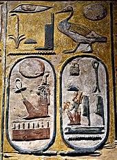 Каменное лицо, высеченное цветными иероглифами.  Внизу видны два картуша - яйцевидной формы с иероглифами внутри.
