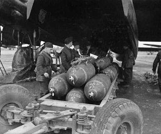 "RDX - Preparing to load 1,000-lb MC bombs into the bomb-bay of an Avro Lancaster B Mark III of No. 106 Squadron RAF at RAF Metheringham, prior to a major night raid on Frankfurt. The stencilled lettering around the circumference of each bomb reads ""RDX/TNT"""