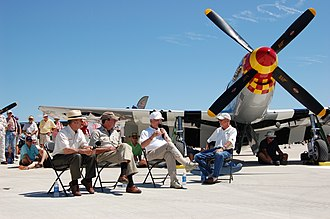 Bud Anderson - Bud Anderson as he appeared in 2011. Anderson is seated second from the right, in the white cap. This picture was taken at EAA AirVenture 2011, as Anderson tells a large crowd his war stories. He sits next to a P-51 Mustang painted in his World War II colors.