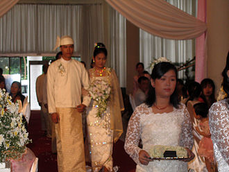 Weddings in Myanmar - A wedding procession, with the groom and bride dressed in traditional Bamar wedding costume, reminiscent of royal attire.