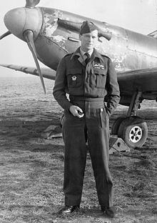 A full length picture of a man in RAF uniform. He stands in front of a parked aircraft, with one hand in a pocket and holding a pipe in the other.