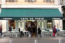 Vue de face d'un café avec son store vert tiré sur lequel est écrit en blanc «Café de Turin» en lettres majuscules.