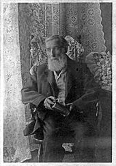 Black-and-white photo of an old man with a long white beard