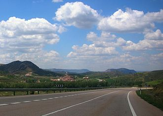 Castel de Cabra - N-211 road with Castel de Cabra town and the Sierra de San Just mountains in the background