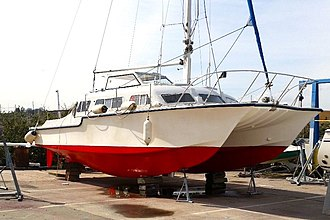 """Catalac catamarans - A Catalac 9M ashore, showing underwater hull profile with pronounced """"rocker""""."""