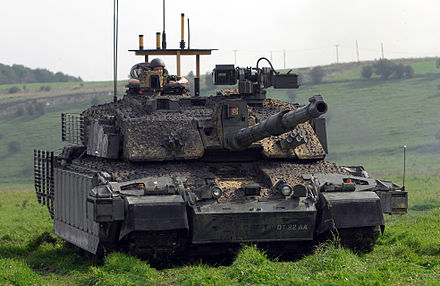 Challenger 2 with armour upgrades to the sides of the turret, skirts, bar armour to rear. Smoke grenade launchers visible on turret front. Counter-IED ECM antennas are on the platform on the turret, and additional ECM equipment overhangs the left and right front fenders. A remote controlled weapon systems (RCWS) has also been fitted to the turret.
