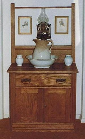 Commode - A washstand with pitcher (jug) and towel rack, sometimes known as a commode.