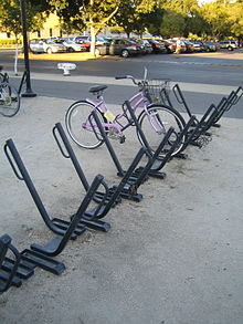 An array of sixteen or so parking spots for bicycles. Each is a square metal bar angled at 45 degrees from the ground with a parallel loop of thinner round tubing at the top. They are set in a row with the bars pointing in alternating directions. A pink ladies' bicycle with a shipping basket is parked in one. Another row of them is mostly out of frame to the left with a mountain bike parked in it. In the background is a car park with trees.