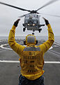 Defense.gov News Photo 110624-N-PB383-260 - Petty Officer 3rd Class Lazarus Bullock enlisted landing signalman aboard the guided-missile frigate USS McClusky FFG 41 guides an SH-60R Sea.jpg