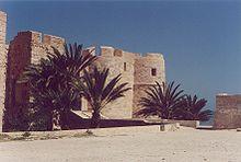Façade du fort Borj El Kebir de Houmt Souk, partiellement masquée par des palmiers.